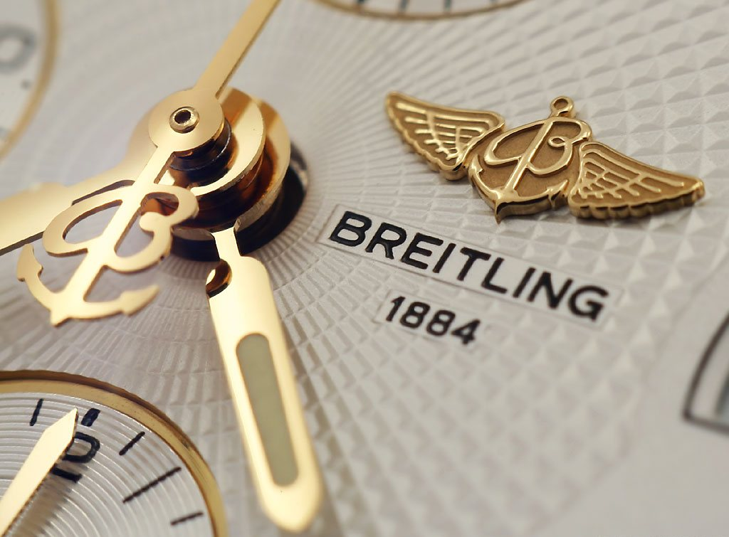 Macro shot of the logos, hands and guilloché dial of a Breitling Chronomat.